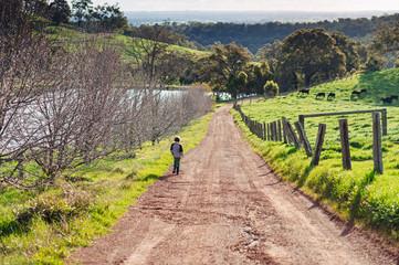 Small boy walking a country road beside a farm