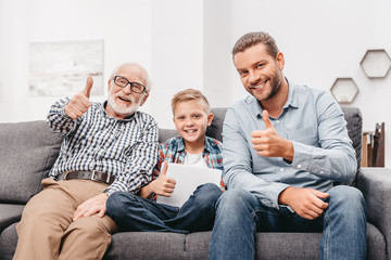 Family on couch showing thumbs up