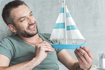 Joyful guy with stubble is playing with small yacht