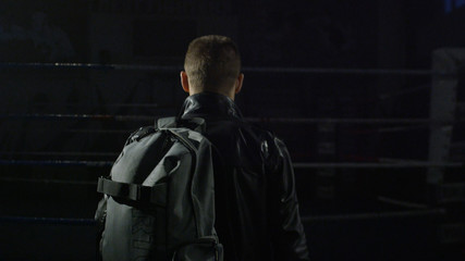 Man in a jacket and bag in the gym. Man going with bag after training. Man going to the gym
