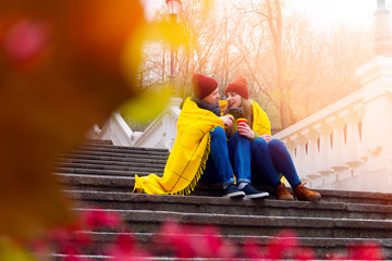 Romantic couple of teenagers female / male in love sitting on stairs in park holding cups of coffee / tea and covered by yellow warm plaid / wrap in autumn