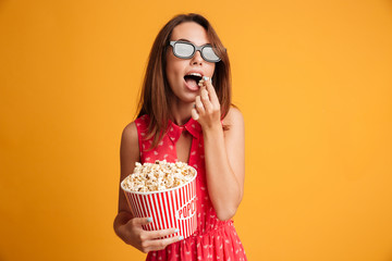 Beautiful young brunette woman in 3d glasses and red dress eating popcorn, looking at camera