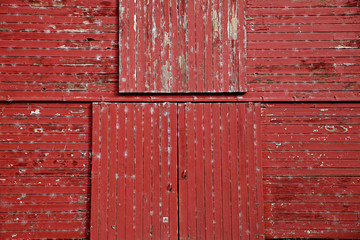 graphic close up photo of old red wooden barn patina doors in the country