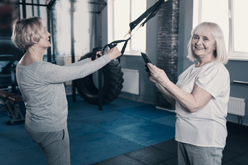 Smiling woman taking photo of friend exercising with suspension trainer