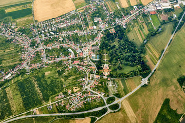 Aerial view of unidentified village in summer countryside during sunset.