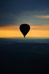Aerial view of summer countryside during sunset with silhouette of hot air balloon