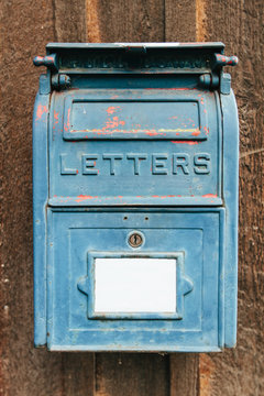 Old blue mailbox hanging on a wooden panel wall of a small, rustic building
