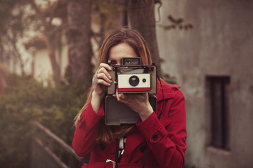 Woman taking a photo with an old vintage film camera