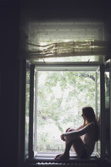Woman Sitting At Window Sill