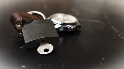 Lock with key on wristwatch concept of importance of time