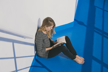 Blond woman sitting against a wall reading a book