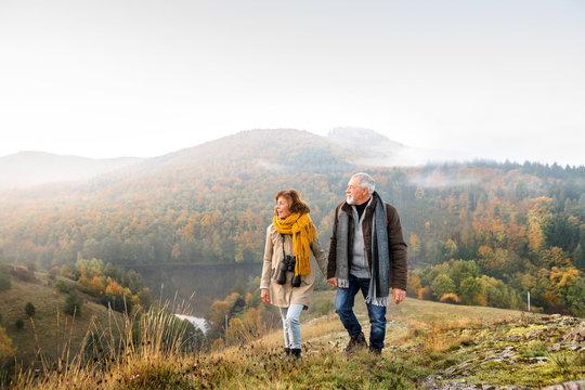 Senior couple on a walk in an autumn nature.