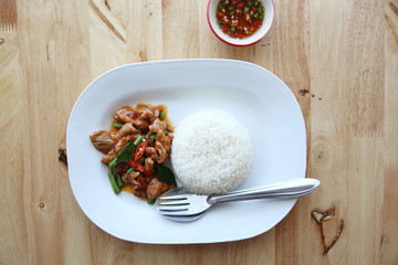 fried pork with thai curry and rice on wood background , Thai food