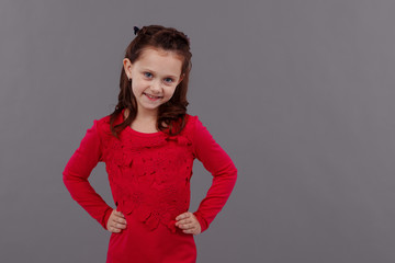 Portrait of a little girl in red dress on grey background emotions.