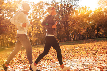 Couple of runners jogging a the city park.Sunset and autumn concept.