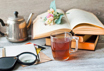 Books, notepad for notes and a cup of tea on the table. The concept of education, recreation and relaxation. The style is retro.