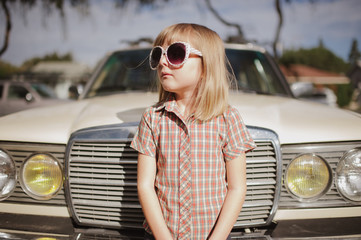 young girl standing in front of old car with sunglasses on
