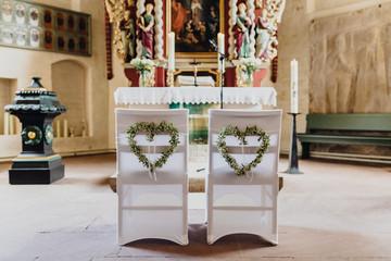 Geschmückte Stühle in der Kirche für eine Trauung