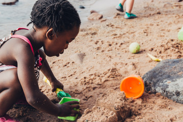 African American Girl Playing on A Beach With Toys