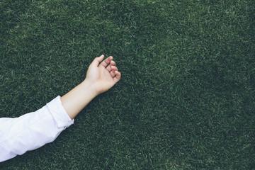 Teenage boys hand and arm on grass