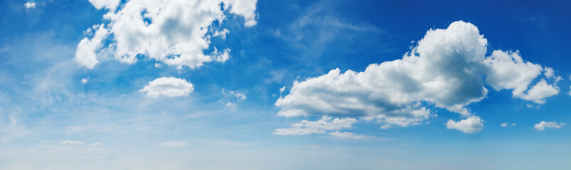 Panorama of blue sky with white clouds at sunny day. Abstract natural background with thick fluffy clouds