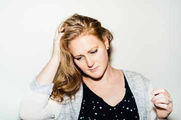 Portrait of a woman playing with her hair in from of a white background