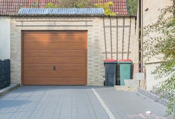 Braunes Garagentor und Mülleimer auf einem Garagenhof