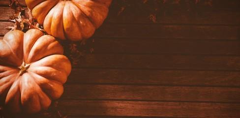 Orange pumpkins with autumn leaves on table