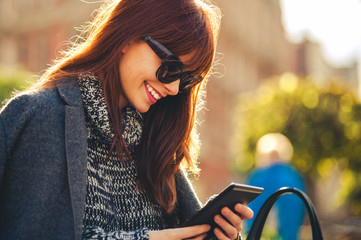 Smiling woman using tablet or ebook reader sitting on the city, urban scene