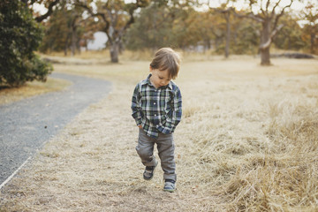 Young mixed race (asian caucasian) toddler boy exploring the oudoors walking