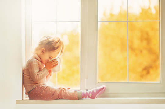 Little cute Kid Girl sitting by window indoor holding cup of hot drink cocoa enjoying autumn forest background. Season Beauty fashion Children concepts. Fall season