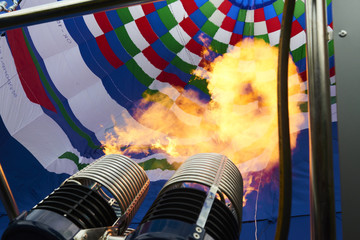A burner with its super hot flame light up inside of a hot air balloon as it is inflated for an  flight.