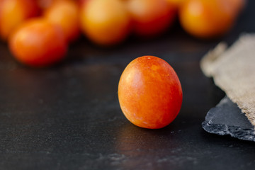Fresh and ripe wild plum or cherry-plum on black surface.