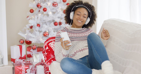 Young girl relaxing on a sofa in front of the decorated tree listening to Christmas music on her mobile phone on stereo headphones