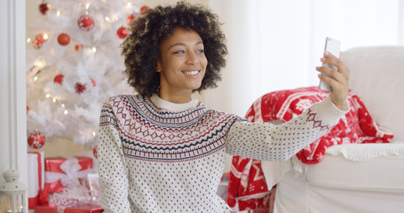 Happy young woman posing for a Christmas selfie on her mobile phone in front of a red and wite themed tree and gifts in a festive living room.