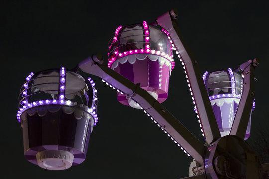 Small ferris wheel fairground ride illuminated against a black sky