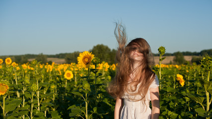 Girl with blond hair in a field of sunflowers