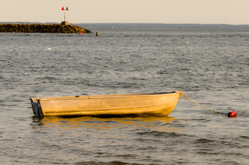 Empty small boat at sea during sunset