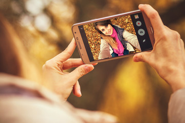 young happy woman doing autumn selfie on smartphone for social network on nature