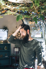 Young Man With Beard in Front of Vintage Trailer