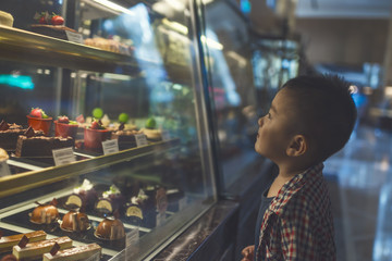 Kid looking at cakes in cabinet