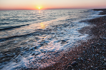 beautiful gentle sunset at the sea, bright sun and pebble beach
