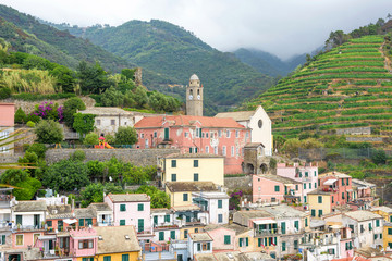 View to city, belltower of the church Santa Margherita and green mountains of Vernazza, Cinque Terre, Italy