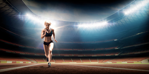 young female athlete running on track. illuminated night track and field stadium