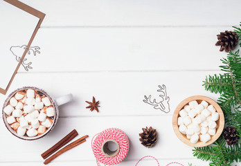 Hot cocoa with marshmallows and other Christmas accessories on the white wooden backgrond