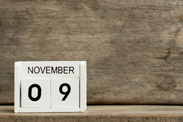 White block calendar present date 9 and month November on wood background