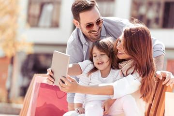 Happy family taking selfie in city.