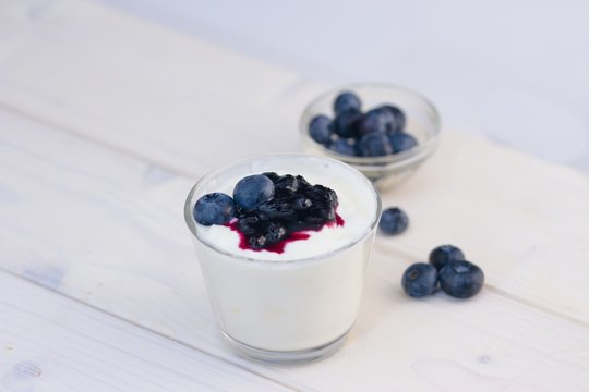 Glass cup of yogurt with blueberries on white table and white background