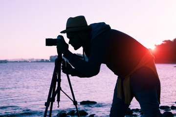 Silhouette of photographer at sunset on the beach using camera on tripod - Concept of travel, hobby and photography equipment