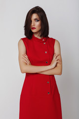 Wall Mural - Young woman posing in red dress. Fashion makeup